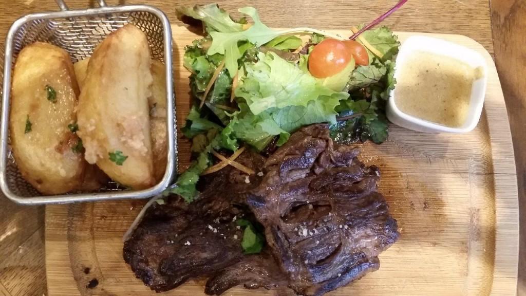 Pièce du boucher sur planche, grosses frites au couteau et légumes