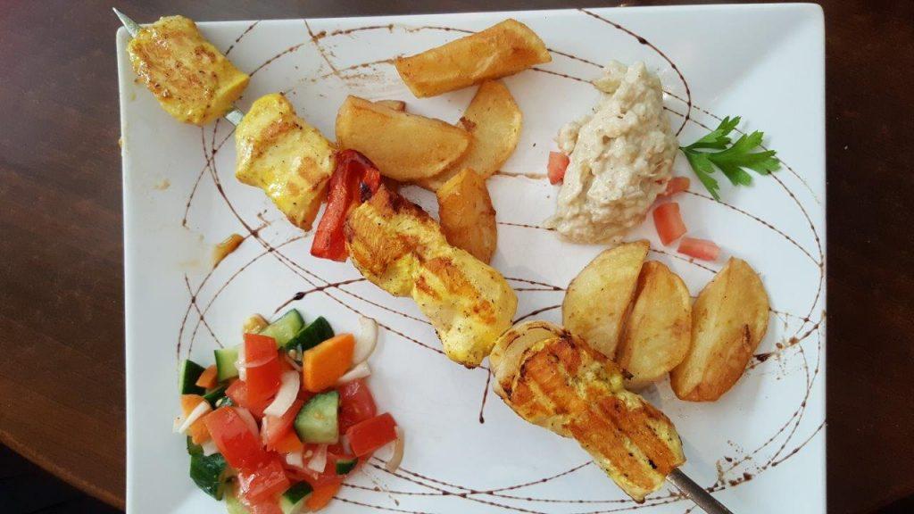 Brochette de poulet, façon caveau, avec caviar d'aubergines, salade, pommes de terre